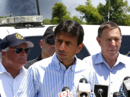 Image: Smoke rises behind Louisiana Governor Jindal during a news conference near the Williams Olefins chemical plant in St. Gabriel