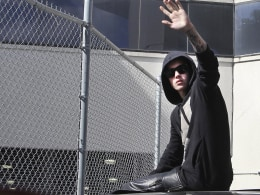 Image: Pop singer Justin Bieber waves from the top of a waiting vehicle after his release on bond from the Turner Guilford Knight Correctional Center in Miami
