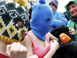 Image: Masked members of protest band Pussy Rot leave a police station in Adler during the 2014 Sochi Winter Olympics