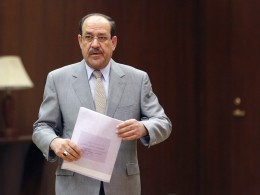 Image: Iraq's PM al-Maliki walks to cast his ballot during parliamentary election in Baghdad