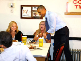 Image: Obama hugs an Hopkins from Los Angeles as he visits Arthur Bryant's Barbeque restaurant in Kansas City
