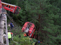 Image: Police and rescue workers help after a passenger train derailed into a ravine near Tiefencastel
