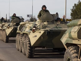 Image: Soldiers, believed to be Russian, ride on military armored personnel carriers on a road near the Crimean port city of Sevastopol