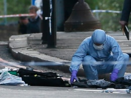 Image: A police forensics officer investigates a crime scene where one man was killed in Woolwich