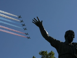 Image: Russian military aircraft trail smoke in the colors of the Russian tricolor above the Monument to Minin and Pozharsky during the Victory Day Parade in Moscow's Red Square