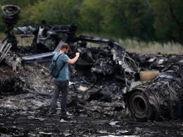 Image: A journalist takes photographs at the site of Thursday's Malaysia Airlines Boeing 777 plane crash near the settlement of Grabovo, in the Donetsk region