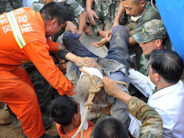 Image: Xiong Zhengfen, 88, is rescued after being buried underneath debris from an earthquake