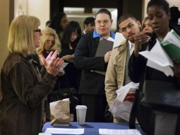 Image: Job seekers adjust their paperwork as they wait in line to attend a job fair in New York