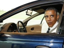 Image: U.S. President Barack Obama looks over his shoulder while driving a simulator at the Turner-Fairbank Highway Research Center in McLean, Virginia