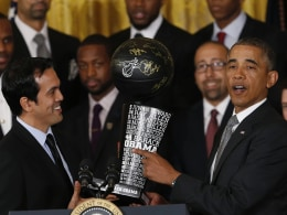 Image: Miami Heat head coach Erik Spoelstra presents a commemorative trophy to U.S. President Barack Obama as Obama honors the NBA basketball champions Miami Heat at the White House in Washington
