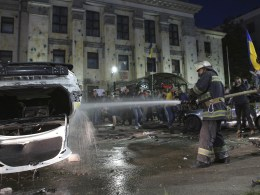 Image: Firefighters pour water onto a damaged car as protesters hold a rally near the Russian embassy in Kiev