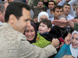 Image: Syrian President Bashar al-Assad greets people during his visit to Ein al-Tinah