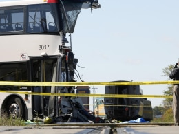 Image: An official photographs the scene of an accident involving a bus and a train in Ottawa