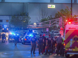 Image: Cobb County Firefighters and paramedics wait outside the Federal Express Ground hub  after a man opened fire inside the building before turning the gun on himself before sunrise in Kennesaw