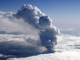 Smoke billows from an erupting volcano b