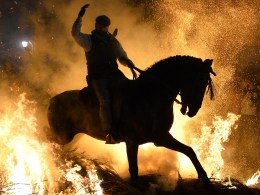 Image: A horse and rider walk over a burning pyre in the central Spanish village of San Bartolome de Pinares.