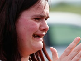 Image: Former pupil Nichola Davies reacts outside Corpus Christi Catholic College after teacher Anne Maguire was fatally stabbed