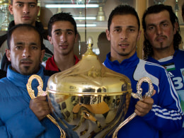 Image: Abu Hammad family members pose with the Yasser Arafat Cup at their club's trophy room in the West Bank village of Wadi al-Nees.