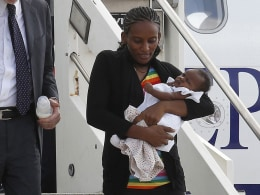 Image: Mariam Yahya Ibrahim of Sudan carries one of her children as she arrives with Pistelli, Italy's vice minister for foreign affairs, holding her other child, and wife Agnese after landing at Ciampino airport in Rome