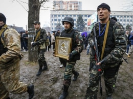 Image: Armed pro-Russian protesters escort a comrade who is carrying an icon, which they said was found in the seized office of the SBU state security service, in Luhansk