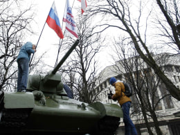 Image: Man installs a flag on a monument, with a Soviet-made tank at the top, near the Crimean parliament building in Simferopol