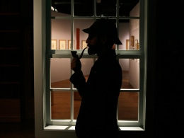 """Image: The curator of the exhibition """"Sherlock Holmes: The Man Who Never Lived and Will Never Die"""" poses with a deerstalker hat and a smoking pipe at the Museum of London"""