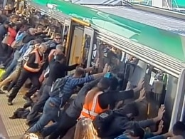 Image: Commuters pushing a train to free a passenger's trapped leg