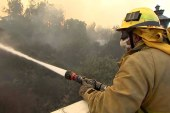 Firefighters work to tamp down flames of...