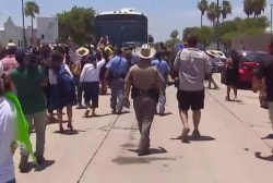 Protestors attempt to block bus that is carrying migrant detainees