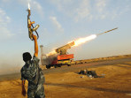 Image: A rebel fighter celebrates as his comrades fire a rocket barrage toward the positions of troops loyal to Libyan ruler Muammar Gaddafi