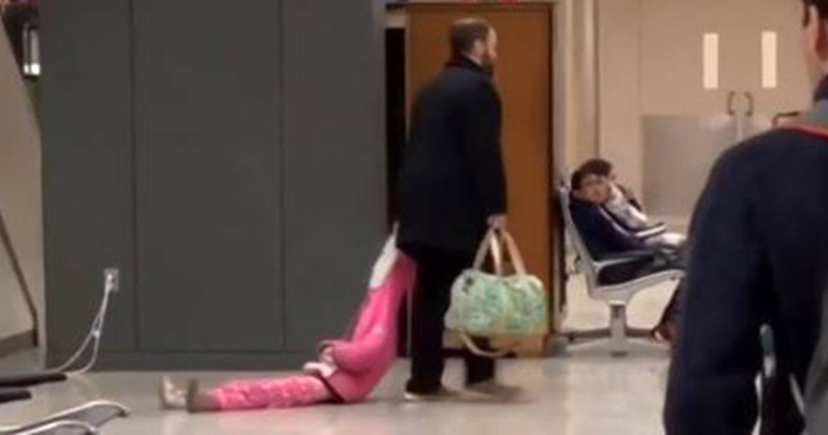 Dad drags daughter around the airport by her hoodie