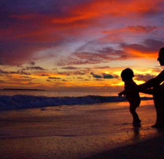 Image: A man plays with his son on the beach at sunrise.