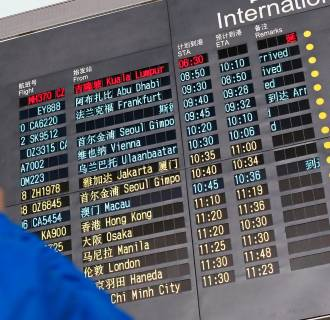 Image: A man takes pictures of a flight information board displaying the details of Malaysia Airlines flight MH370 (top, in red) at the Beijing Capital International Airport in Beijing