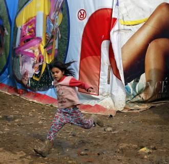 Image: A Syrian child runs in the Fayda Camp some 25 miles east of Beirut