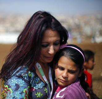 Image: Fatima, 12, is hugged by  Maria Assi, the director of Lebanese NGO