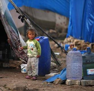 Image: A Syrian refugee child stands outside a tent in the southeastern city of Kilis, near Syrian-Turkish border