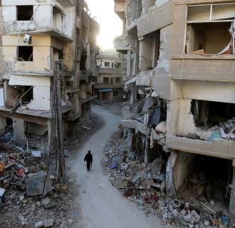 Image: A Free Syrian Army fighter walks between buildings damaged during Syrian Air force air strikes in the Haresta neighborhood of Damascus