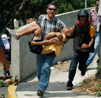 Image: A man carries an injured anti-government protester in San Cristobal
