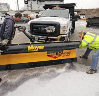 Image: Workers from the Mass. Dept. of Conservation and Recreation put a plow on a truck ahead of an expected winter snow storm in January