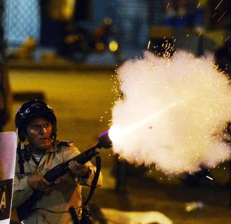 Image: A National Guard member shoots tear gas during an anti-government protest