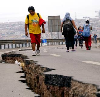 Image: People walk along a cracked road in Iquique, northern Chile
