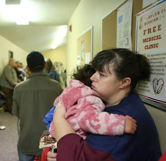 Image: Jaime Grimes hugs her daughter Olivia, 3, while standing in a food line with her in Lincoln, Nebraska.