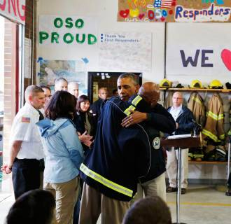 Image: U.S. President Barack Obama hugs a first responder after touring the mud slide damage in Oso, Washington