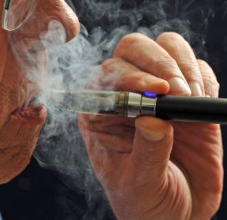 A smoker puffs on an e-cigarette.