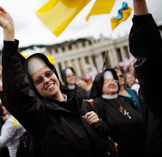 Image: Nuns wave as Pope Francis is driven through the crowd after presiding over a solemn ceremony in St. Peter's Square