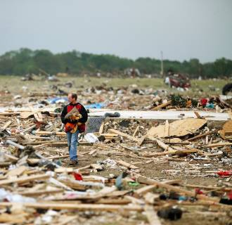 Image: Resident Mark Wade looks through debris after the area was hit by a tornado in Vilonia, Ark.