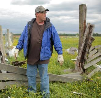 Image: Cattle rancher Preston Scroggin cleans up a corral destroyed by Sunday's tornado at his farm in Vilonia, Ark.