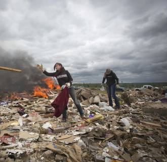 Image: A woman throws a piece of wood into a fire as her friend looks through the rubble of a destroyed house in Vilonia, Arkansas