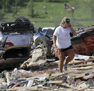Image: Connie Krehel looks through debris after her home was hit by a tornado