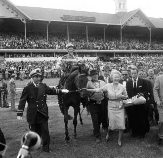 A jubilant Mrs. Katherine Price of Miami, Fla., leads her horse Carry Back from the winner's circle at Churchill Downs after winning the Kentucky Derby on May 6, 1961 in Louisville, Kentucky.